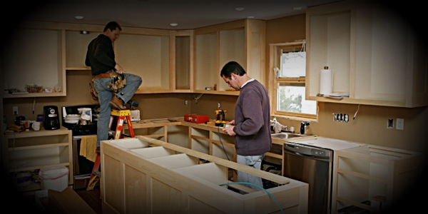 Contractors installing kitchen cabinets